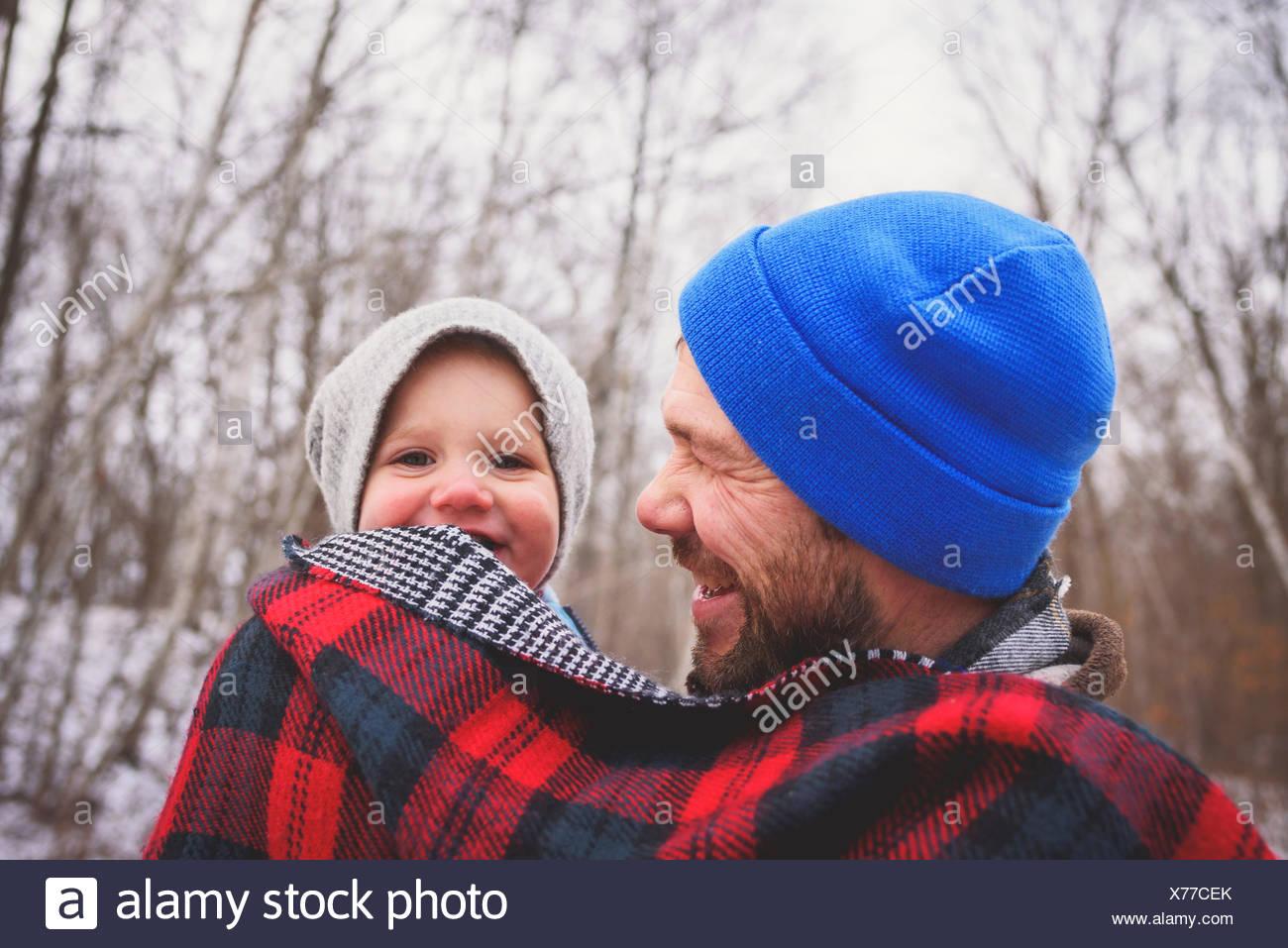 Porträt eines Vaters, der sein Kind in einem Winterwald in einer Decke gehüllt trägt Stockfoto