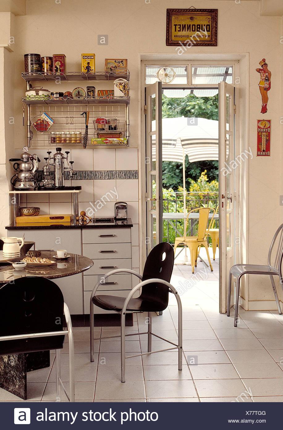 Schwarze Metall-Stühle am Tisch für das Frühstück im Retro ...