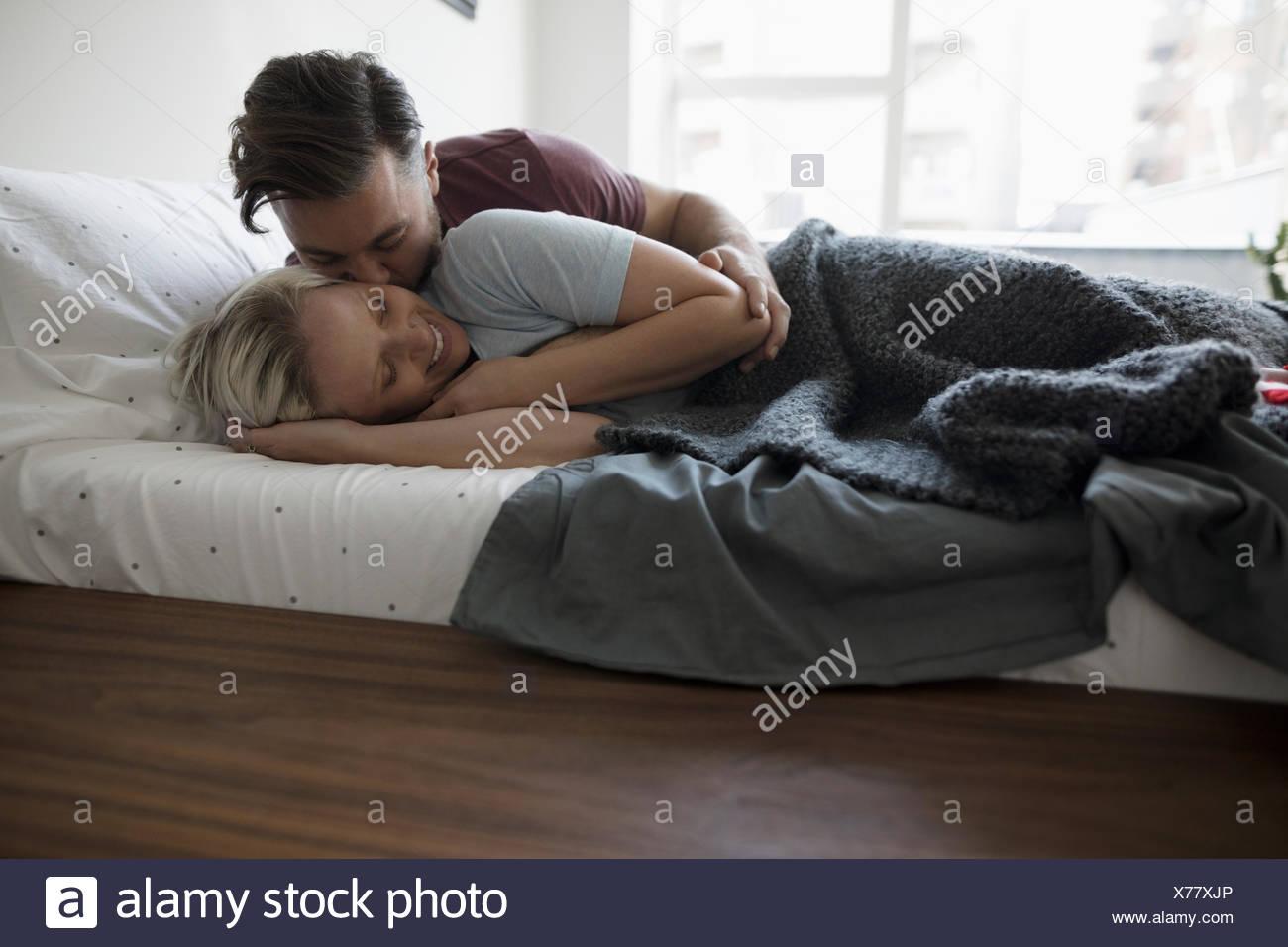 Zärtlich, romantisches Paar küssen und Kuscheln im Bett Stockbild