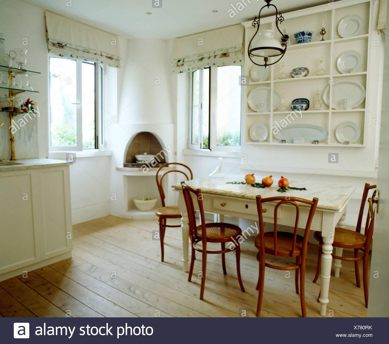 Einfache weiße Regale und gemalten Tisch mit alten Bugholzstühle in ...