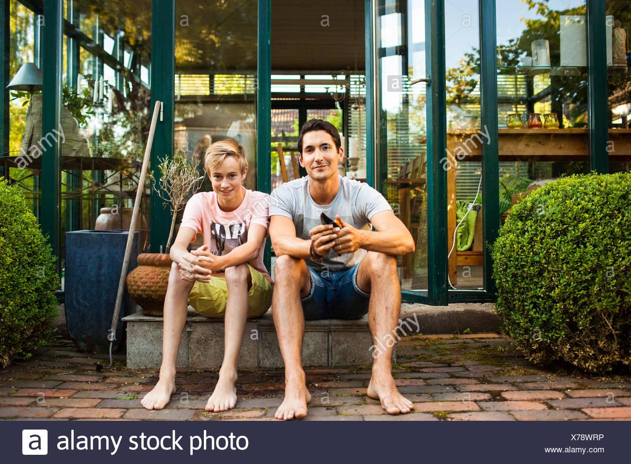 In voller Länge Portrait von Vater und Sohn sitzen vor Haus Stockbild