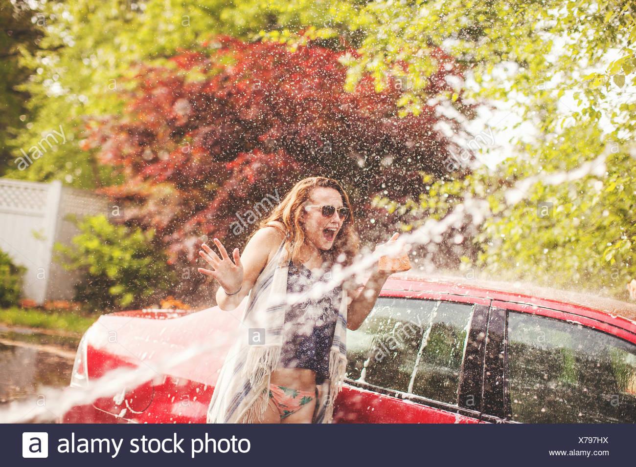 Junge Frau mit Wasser besprüht werden Stockbild