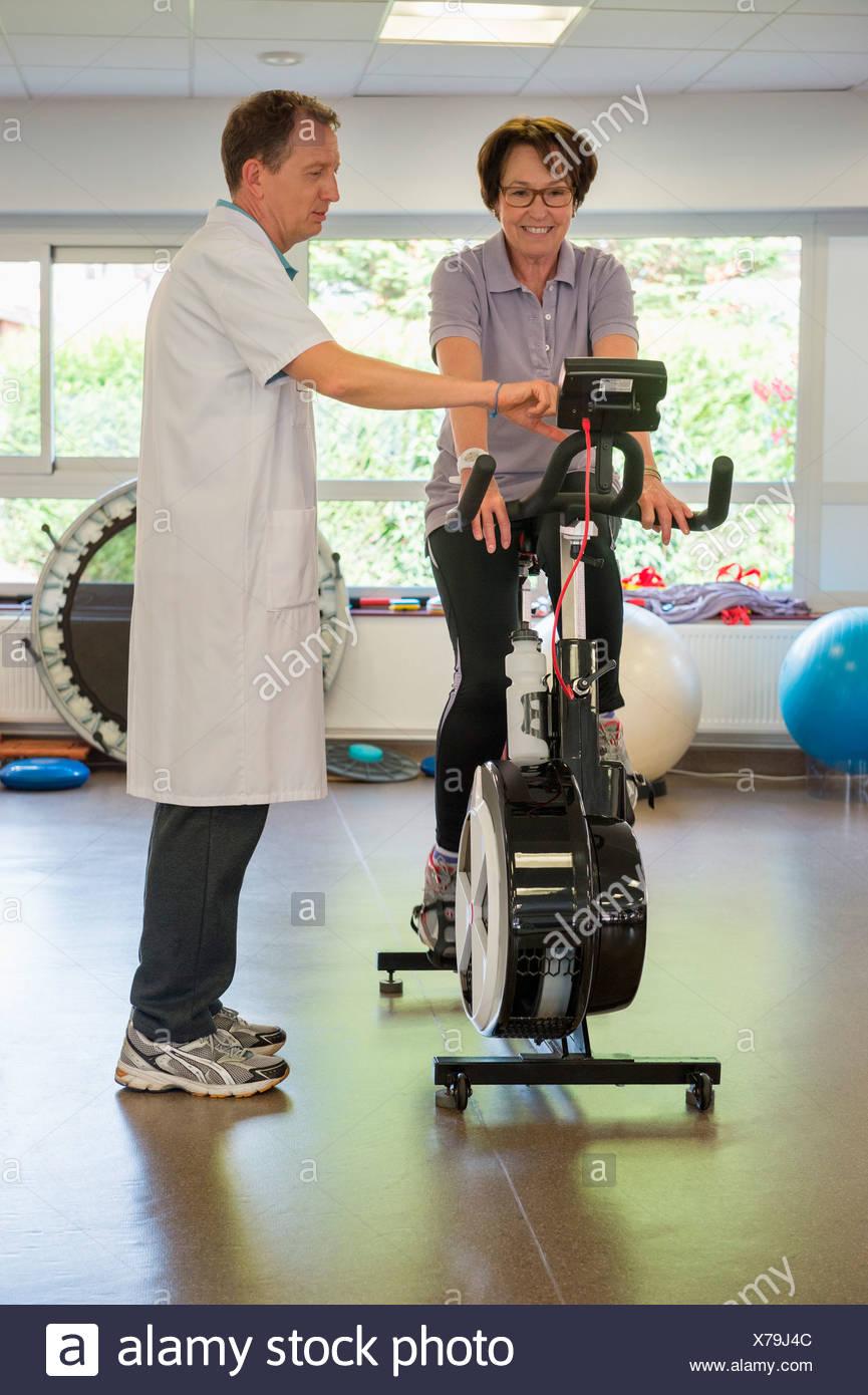 Physiotherapeut hilft einen Patienten einen Heimtrainer zu fahren Stockbild