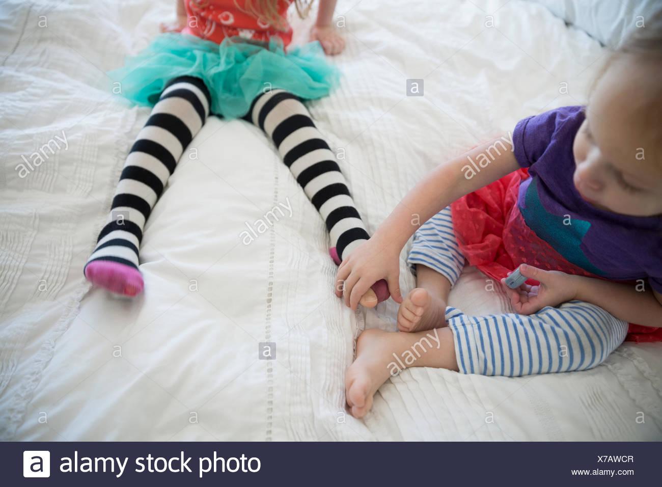 Schwestern in gestreiften Leggings auf Bett Stockbild