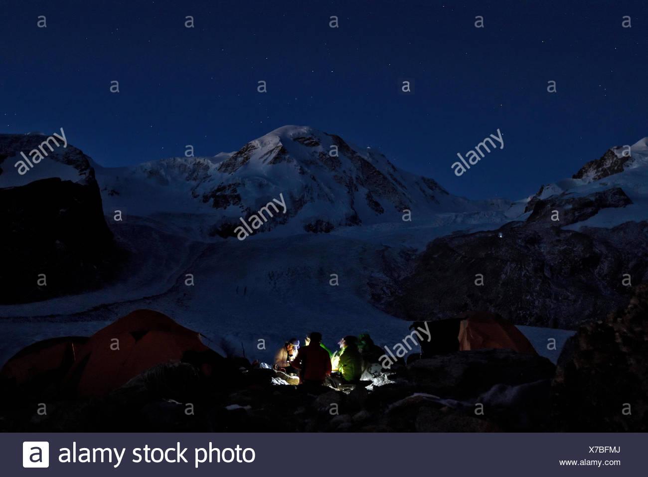 Vier italienische Höhlenforscher genießen ihre letzte Nacht auf dem Gletscher unter dem Sternenhimmel ihrer Mahlzeit. Die schwacher Umriss und Form der Gornergletsc Stockbild