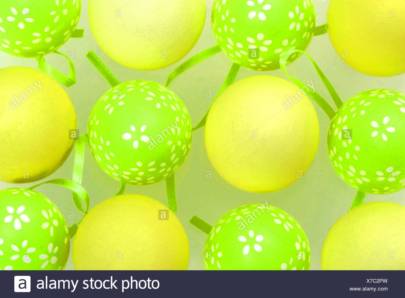 Eiern malte grünen Eiern weißen Blumenmuster, arrangiert abwechselnd blass gelben Eiern grüne Bänder zwischen ihnen Stockbild