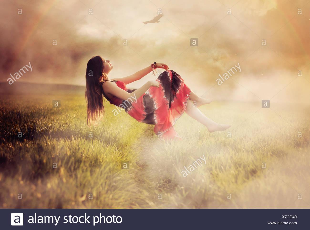 Frau schwebt über einer Wiese, Polen Stockbild