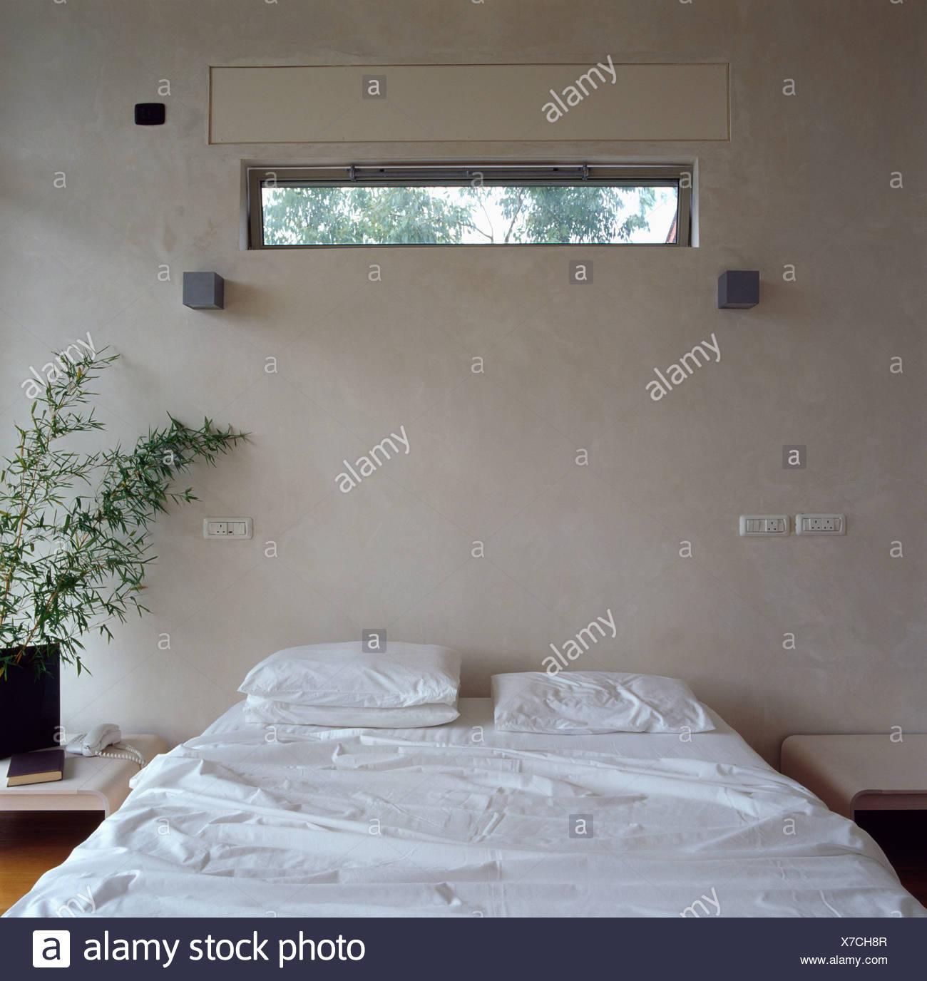 Schmale fenster ber bett mit wei en bettw sche in modernen wei e schlafzimmer stockfoto bild for Schlafzimmer bild uber bett