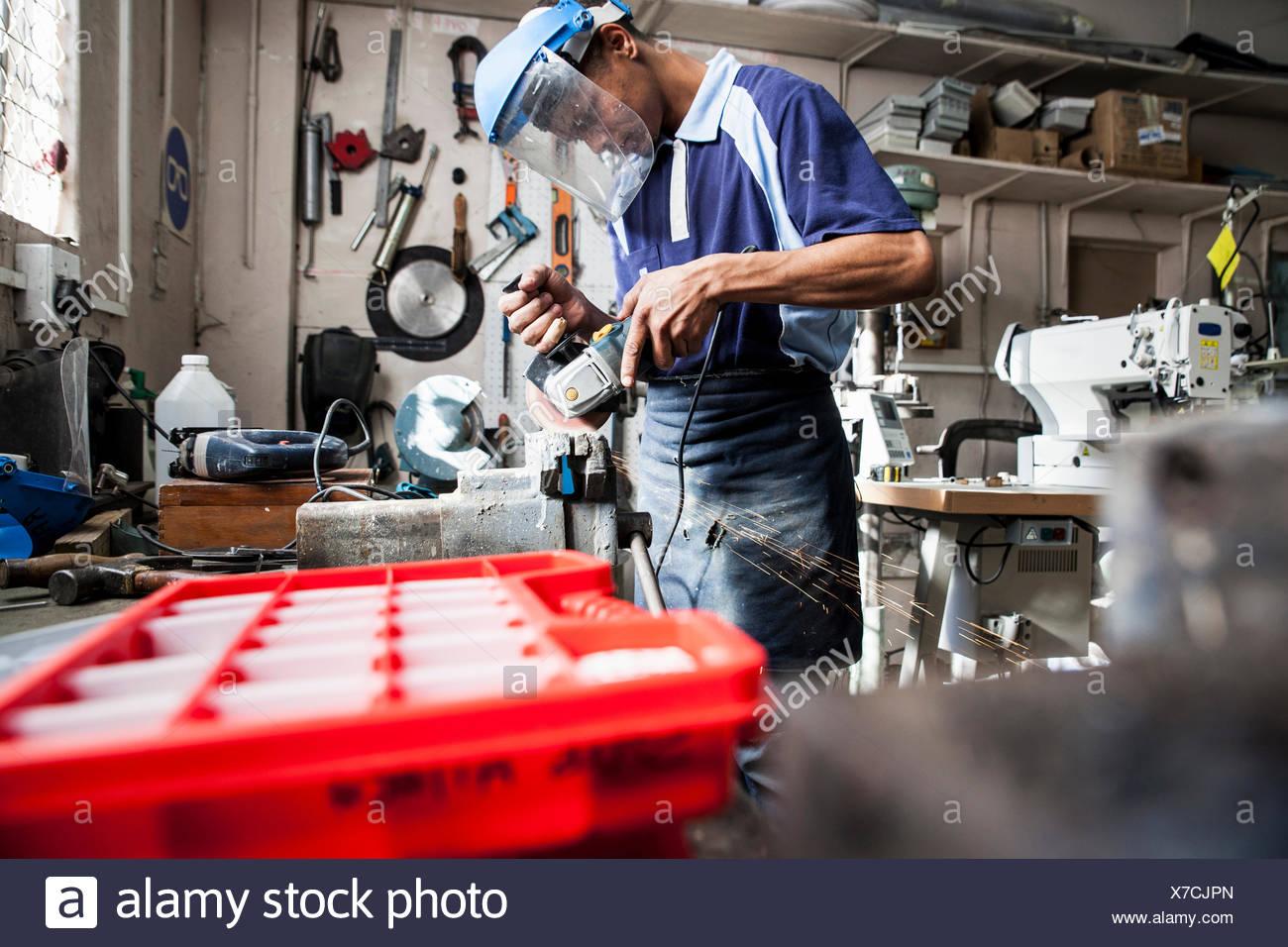 Junger Mann mit Winkelschleifer an Vize-in Reparatur-Werkstatt Stockfoto