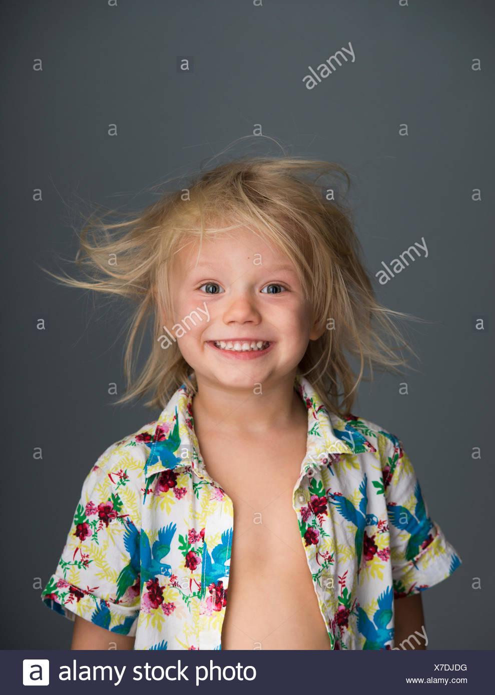 Porträt des jungen mit strubbeligem Haar, Lächeln Stockbild