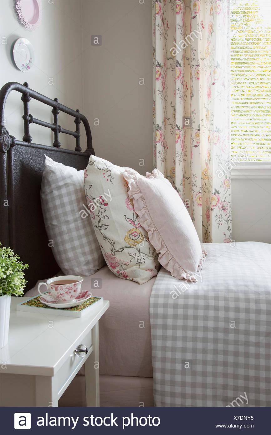 Pastell und karierte Kissen auf Bett Stockbild