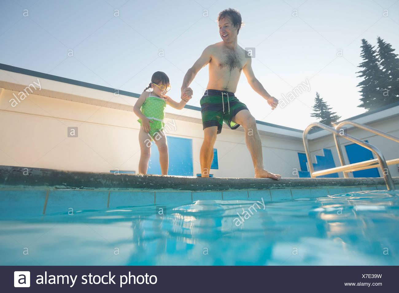 Vater und Tochter ins Schwimmbad springen wird vorbereitet Stockbild