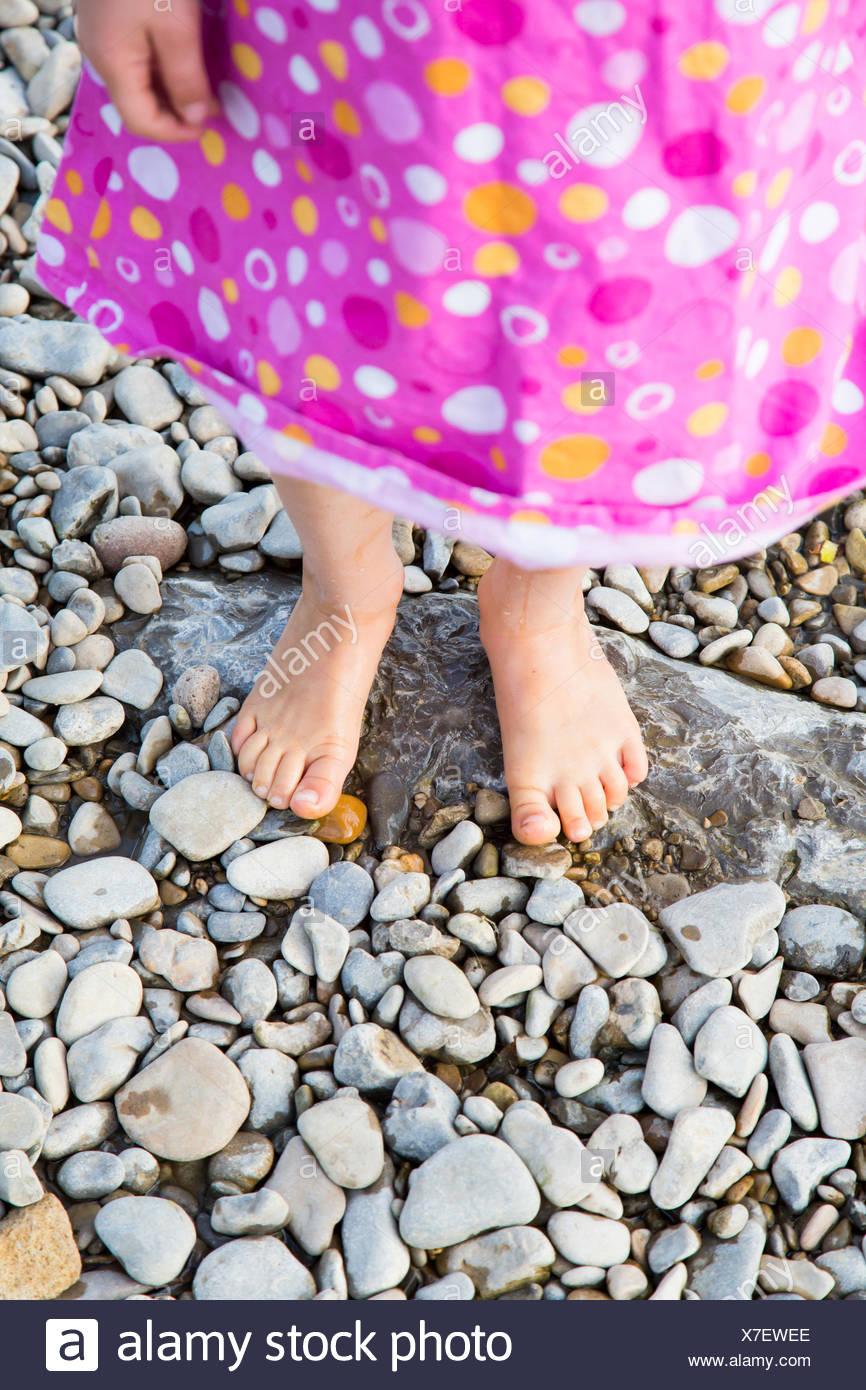 Füße von kleinen Mädchen stehen auf Kieselsteinen im