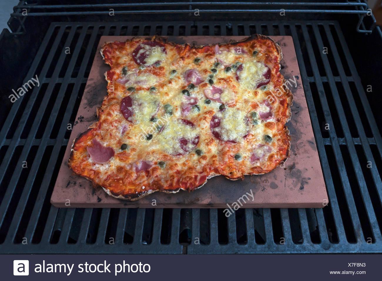 Hausgemachte Pizza Speziale, Tomaten, Gekochter Schinken, Salami Und Käse  Auf Einem Heißen Stein