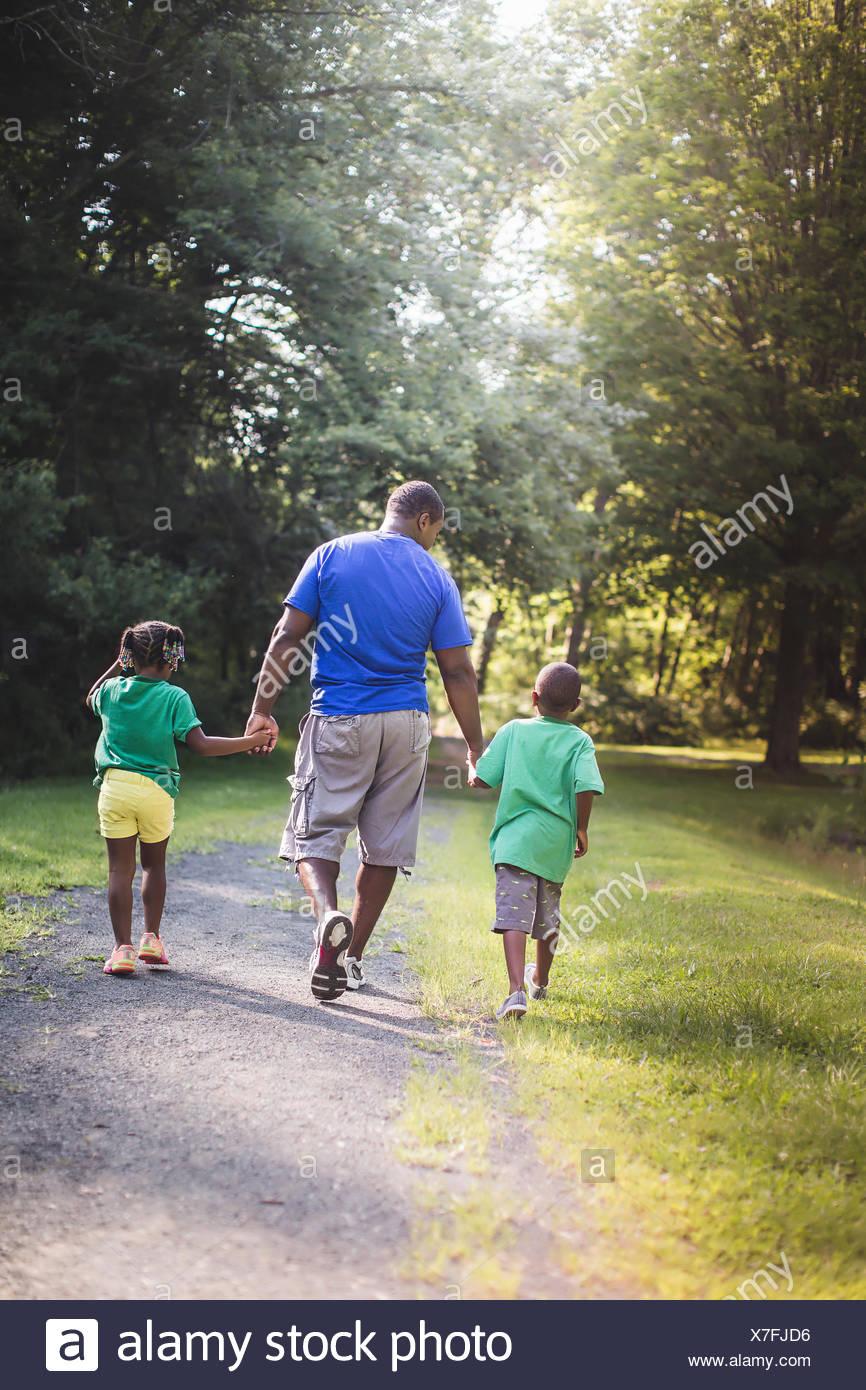 Rückansicht des Vaters Hand in Hand mit Sohn und Tochter im Parkland Eco camp Stockbild