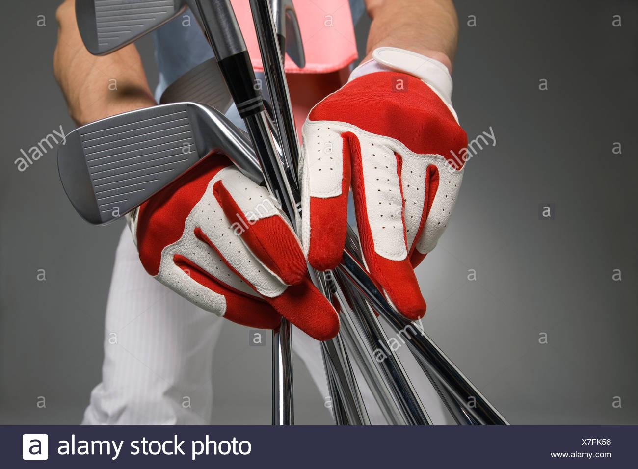 Mittelteil Blick auf jungen Mann, der Golfschläger, hält Studio gedreht Stockbild