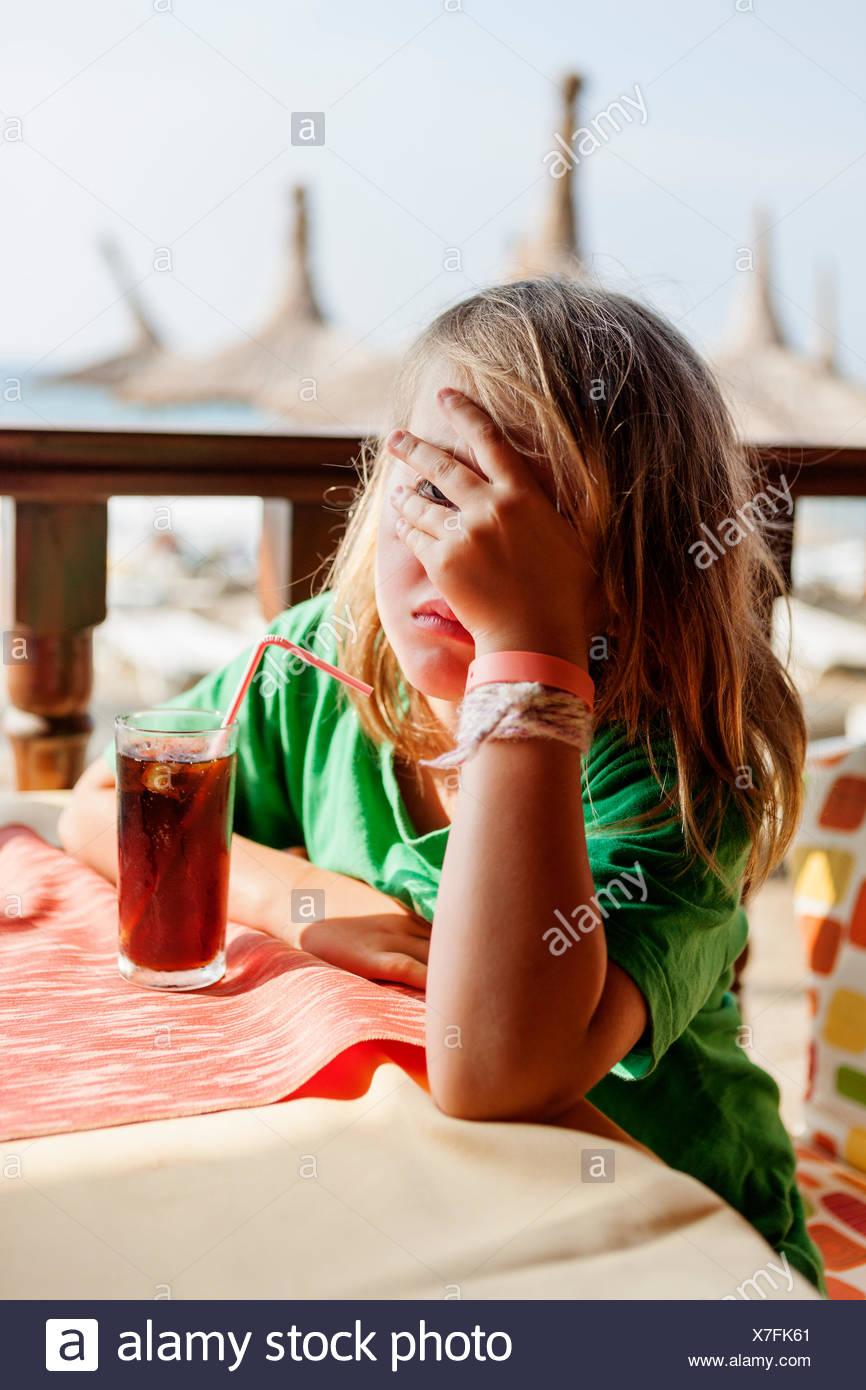 Türkei, Alanya, Mädchen Gesicht (4-5) sitzen am Tisch und bedeckt sie mit hand Stockbild