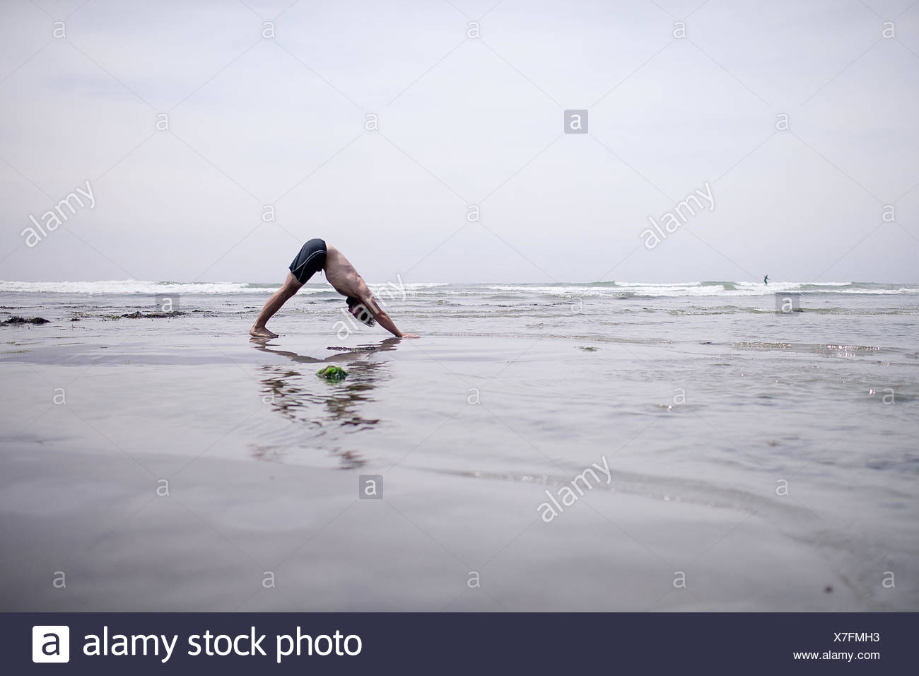 Mann tut unten Hund Yoga-Pose am Strand Stockbild