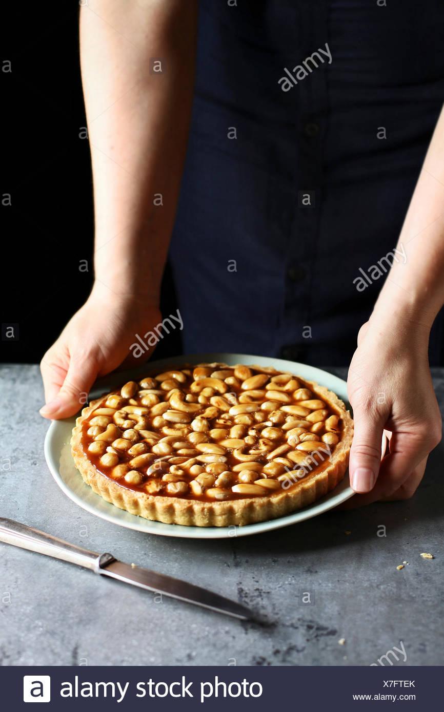 Weibliche Hände halten eine Karamell-Nuss-Torte auf einem Teller Stockbild