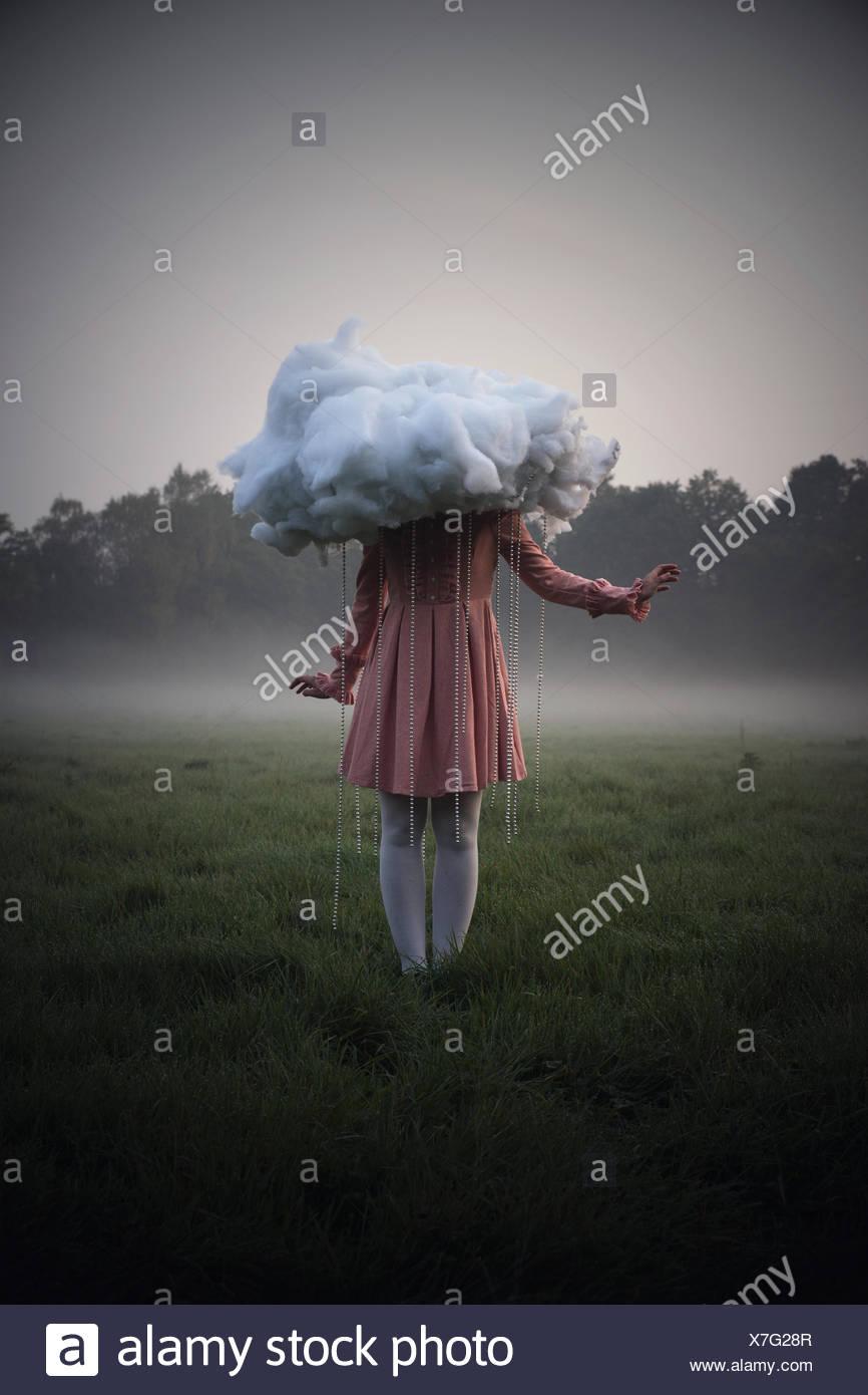 Frau mit einer Wolke bei Regenwetter, surreal Stockbild