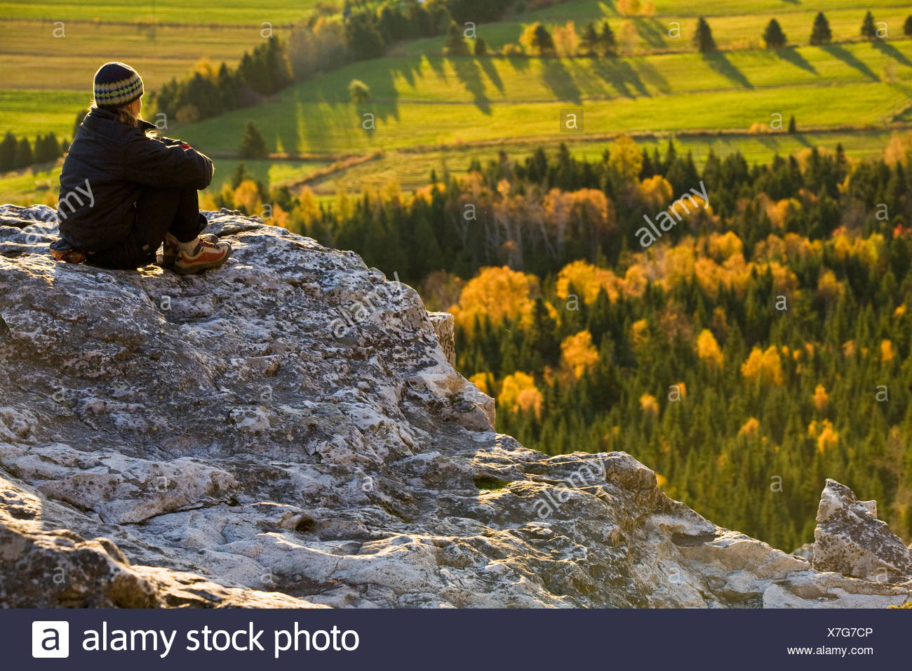 Eine junge Frau, die die Aussicht beim Klettern in Kamouraska, QC Stockbild