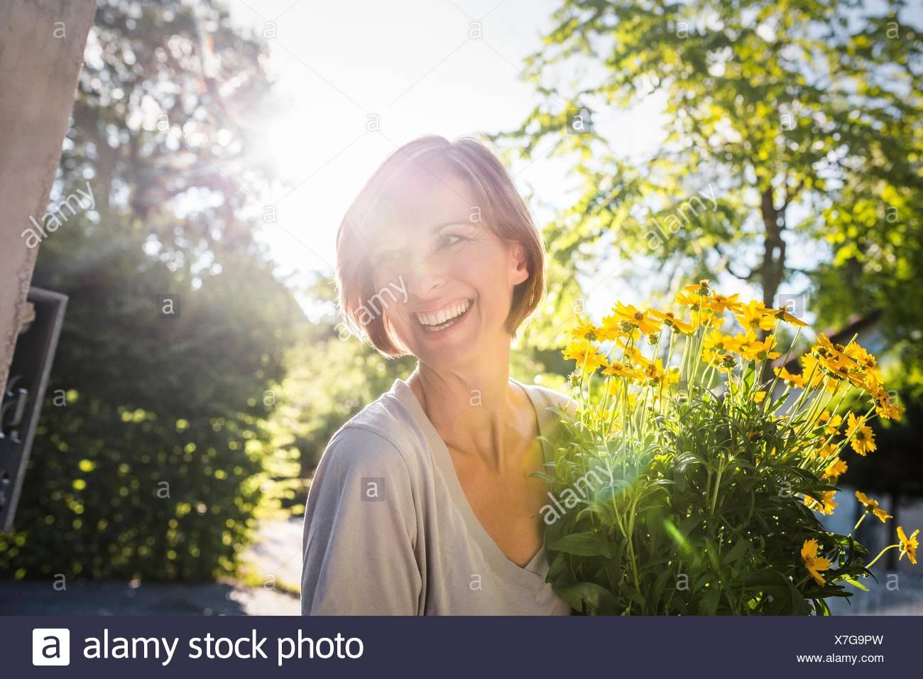 Reife Frau mit gelben Blumen Topf für neues Haus Stockbild