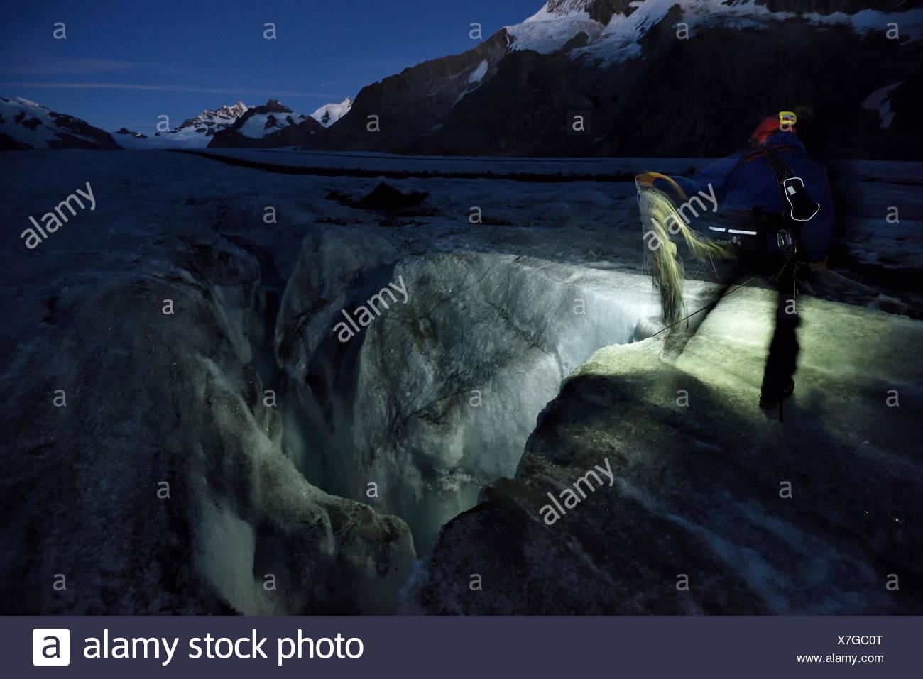 In den frühen Stunden des Morgens bereitet italienischer Höhlenforscher und Glaziologe Alessio Romeo, unten ein Moulin auf Aletschgletschers Stockbild