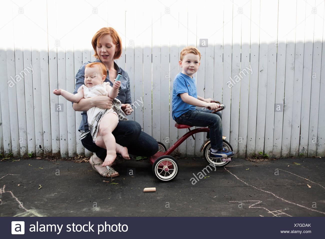 Mutter spielen im Hof mit zwei Kindern Stockbild