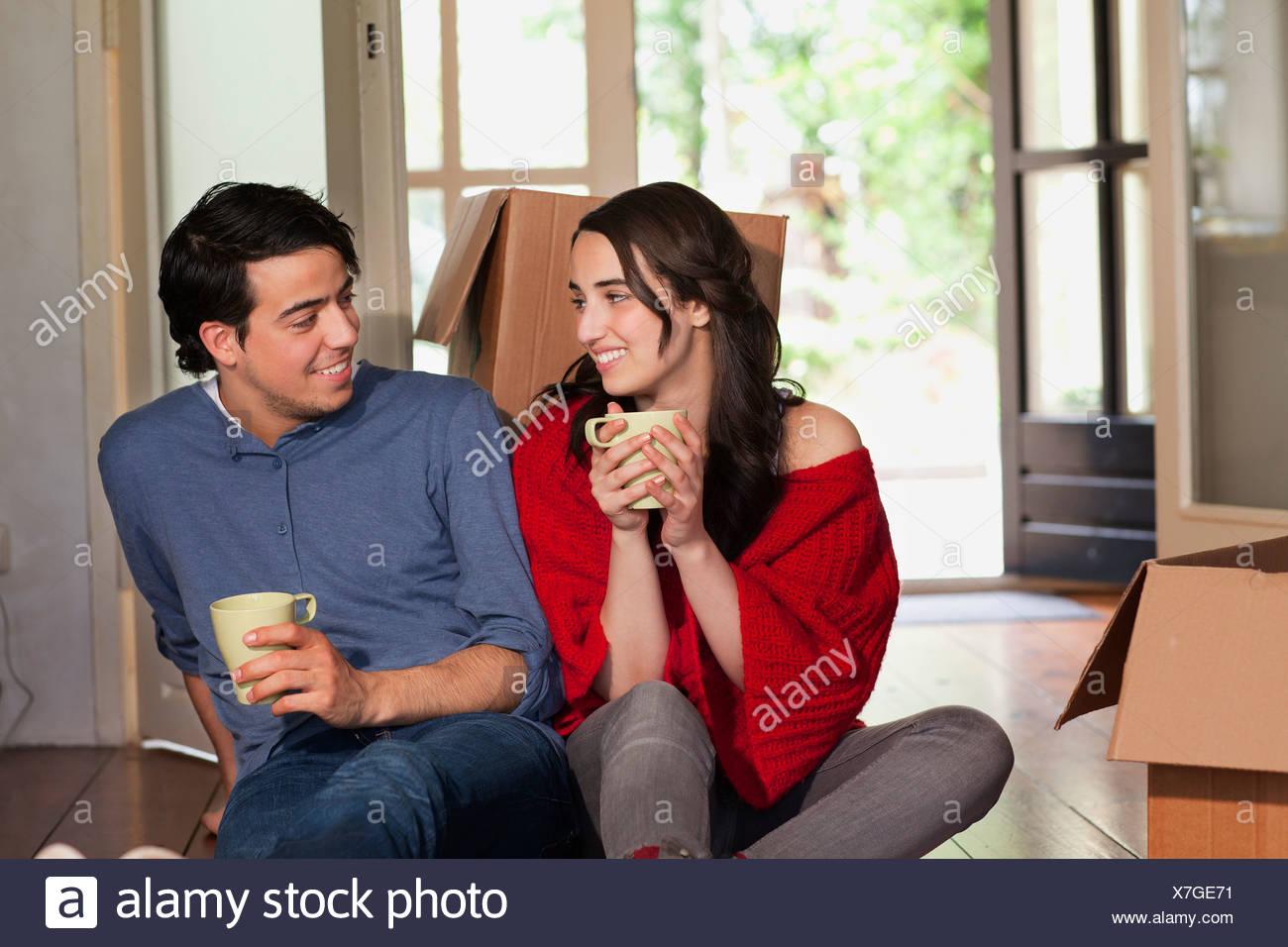 Junges Paar mit Kaffeepause während Umzug Stockbild