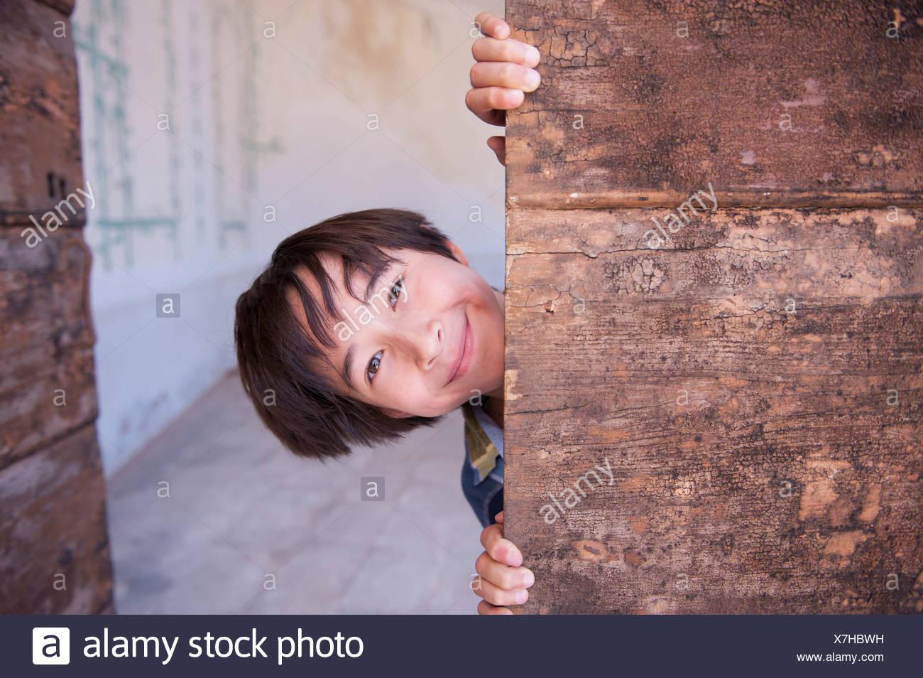 Porträt eines jungen spähen hinter Holz Stockbild