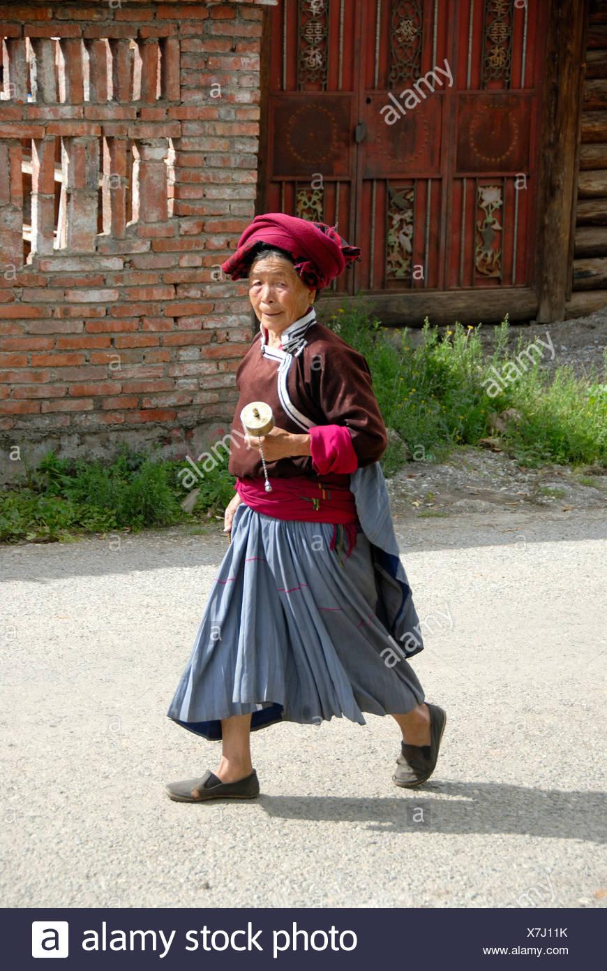 Tibetischen Buddhismus, Ethnologie, Frau von der Ethnie Mosu gekleidet in traditionellen Kostümen eine Gebetsmühle, Luoshui, Lugu schwingen Stockbild