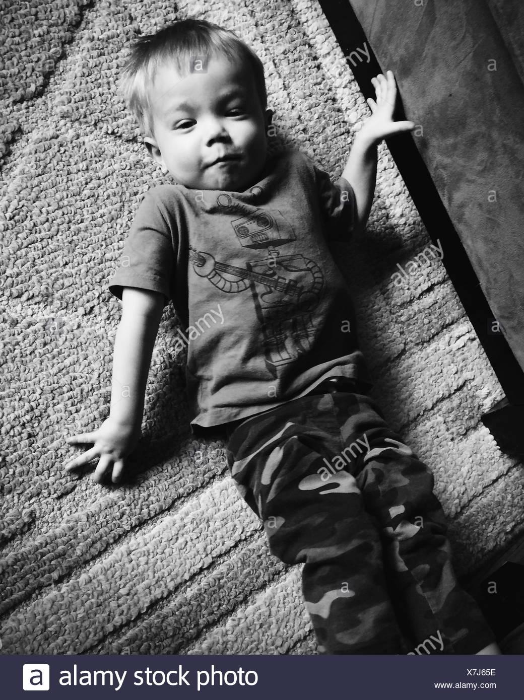 Junge liegend auf Teppich Stockbild