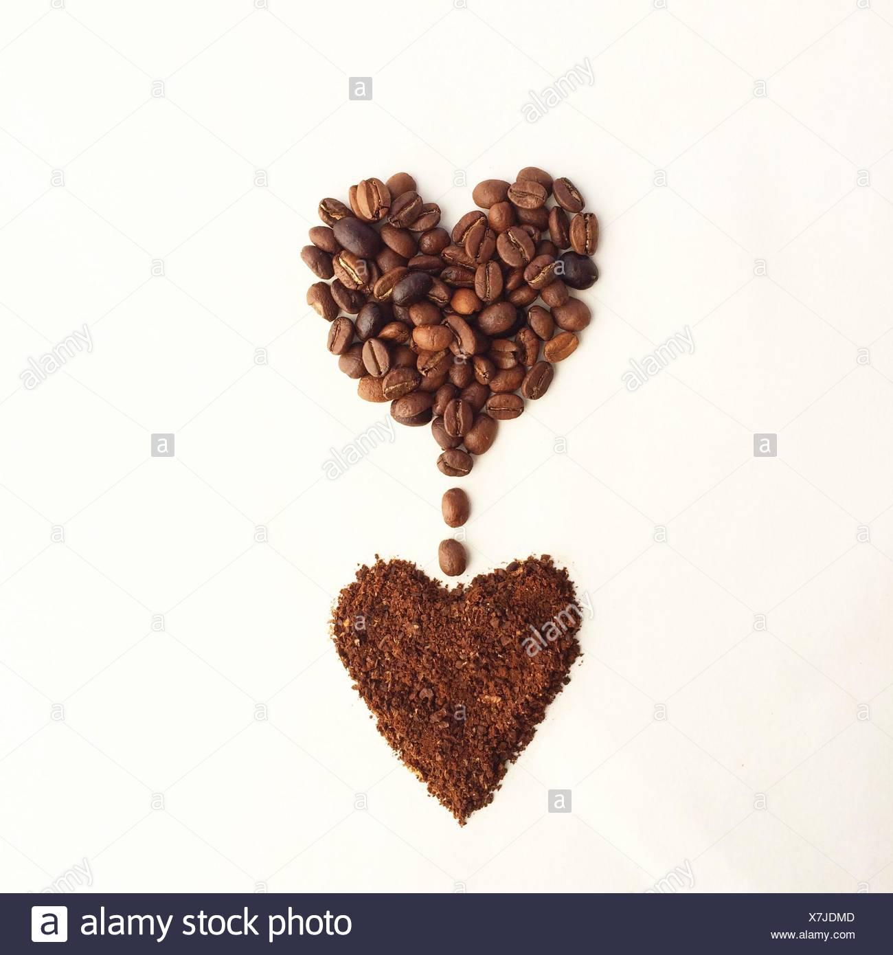 Kaffeebohnen in Form eines Herzens, tropft in ein anderes Herz Form des gemahlenen Kaffees Stockbild