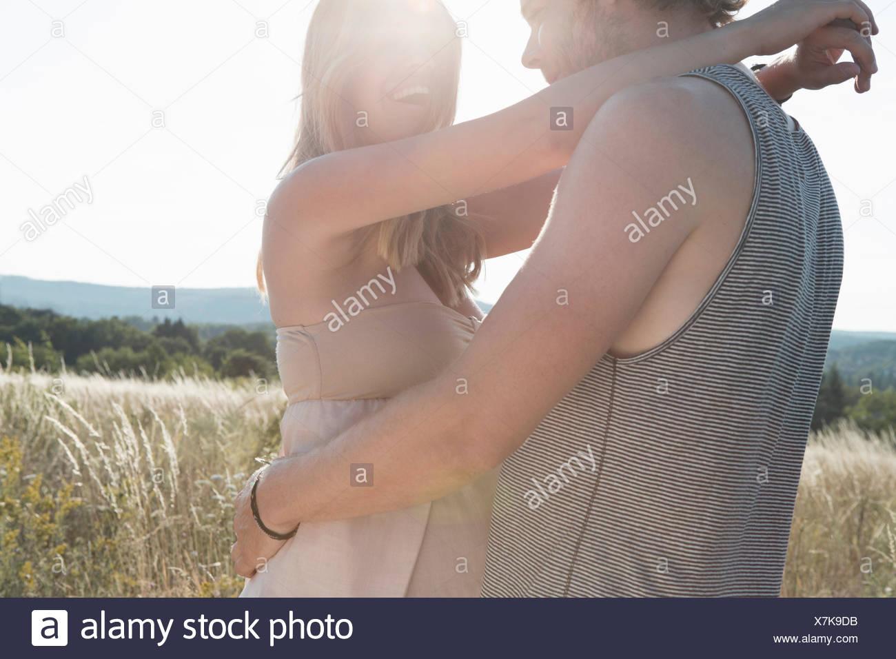 Schwangere junge Frau und Freund umarmt im Feld Stockbild