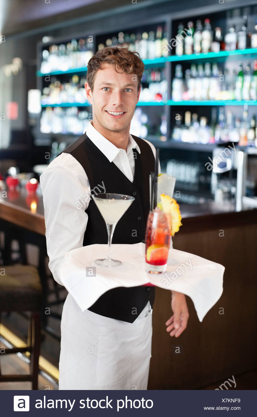 Porträt des Lächelns Barkeeper Holding Tablett mit Cocktails in der Bar Stockbild