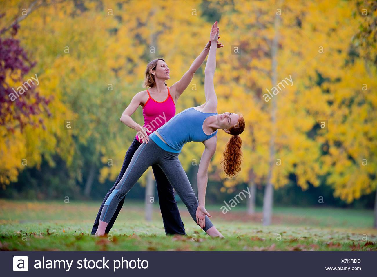 Yoga-Lehrer unterrichten junge Frau im Wald Stockbild