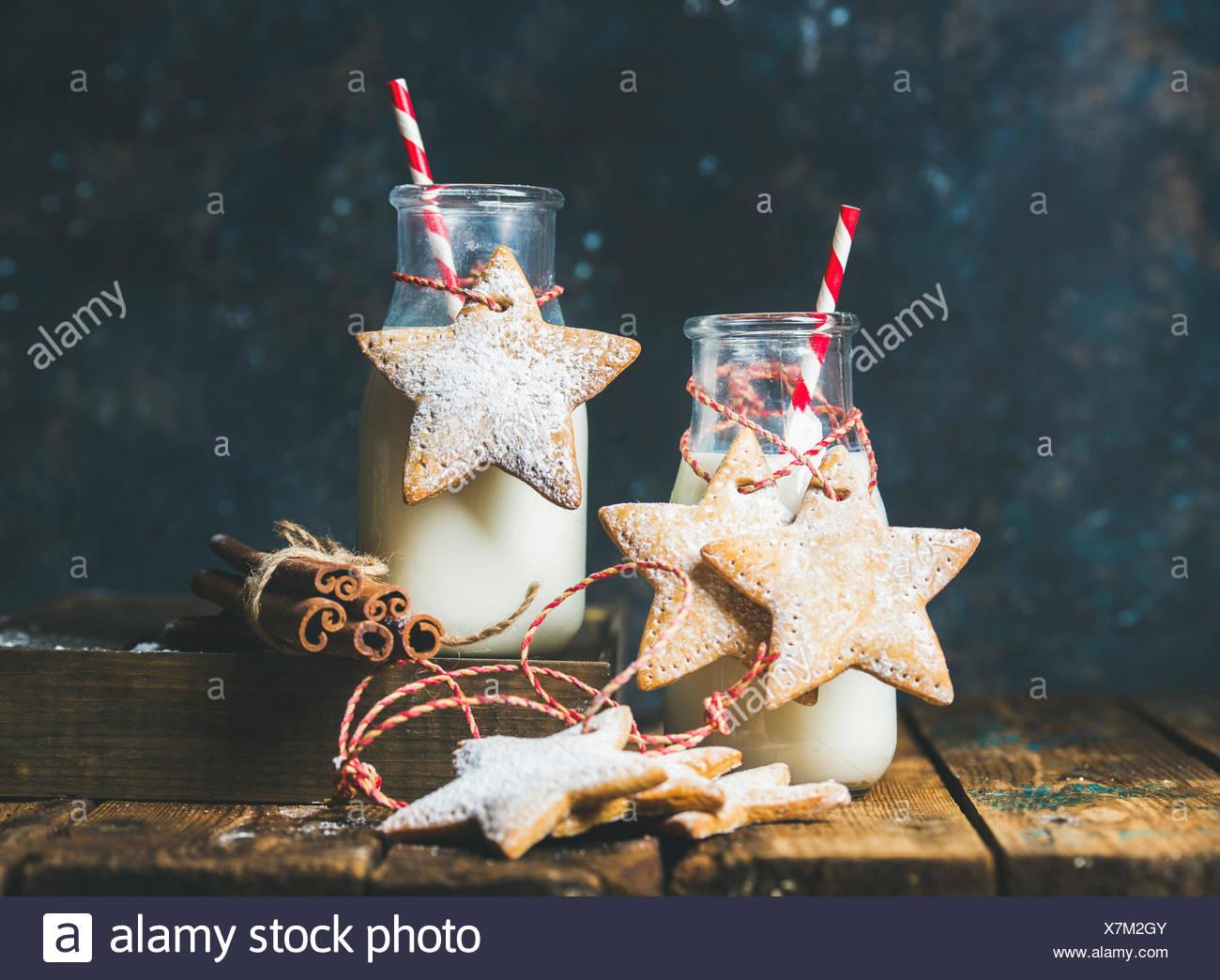 Flasche mit Milch für den Weihnachtsmann, Weihnachten festlich Lebkuchen sternförmige Cookies mit Dekoration Seil, Gewürze auf rustikalen Holztisch, dunkle Blau Zeitmessung Stockbild