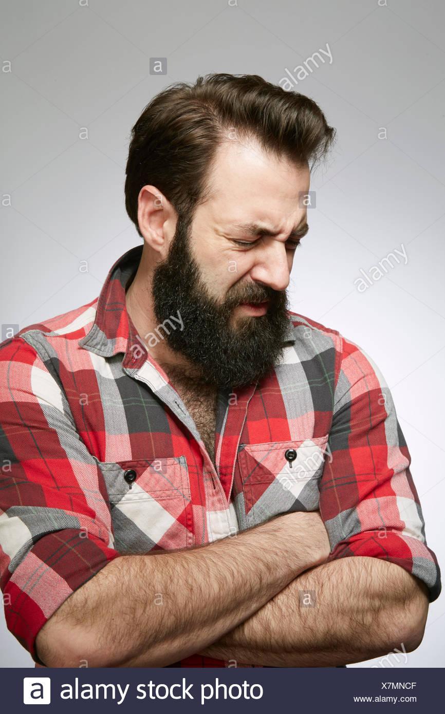 Studioportrait von angstvollen bärtiger jungen Mann mit verschränkten Armen Stockbild