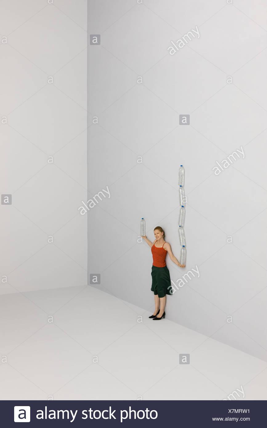 Frau in einerseits hohe Stapel von Wasserflaschen, eine Flasche in der anderen Hand balancieren Stockbild