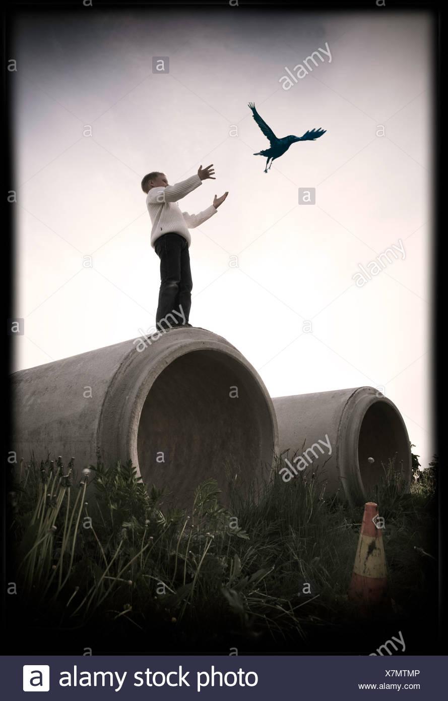 Kleiner Junge steht auf große konkrete Abfluss Freigabe Vogel Stockbild