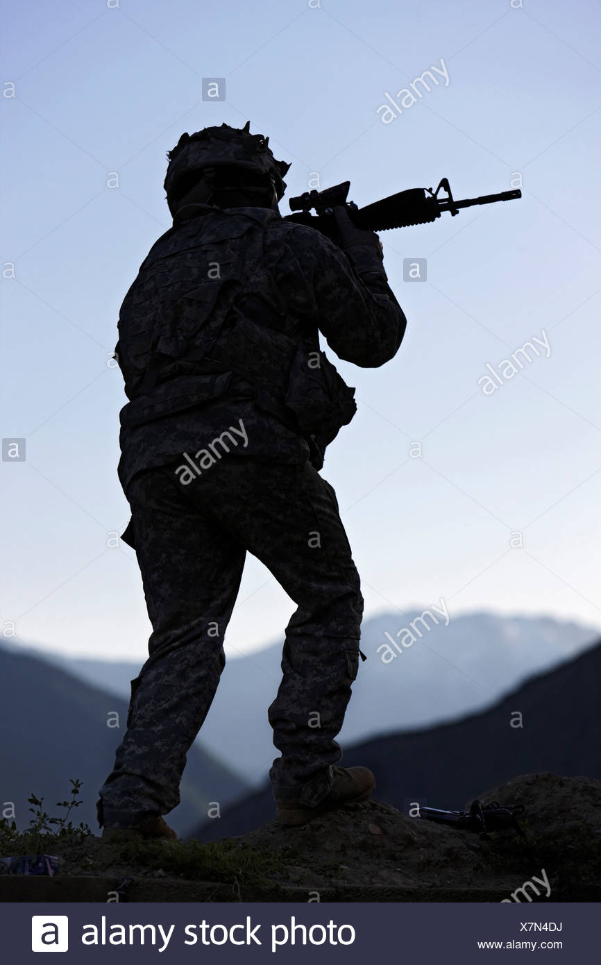 US Armee-Soldat mit dem Ziel seine Waffe bei Sonnenaufgang Stockbild