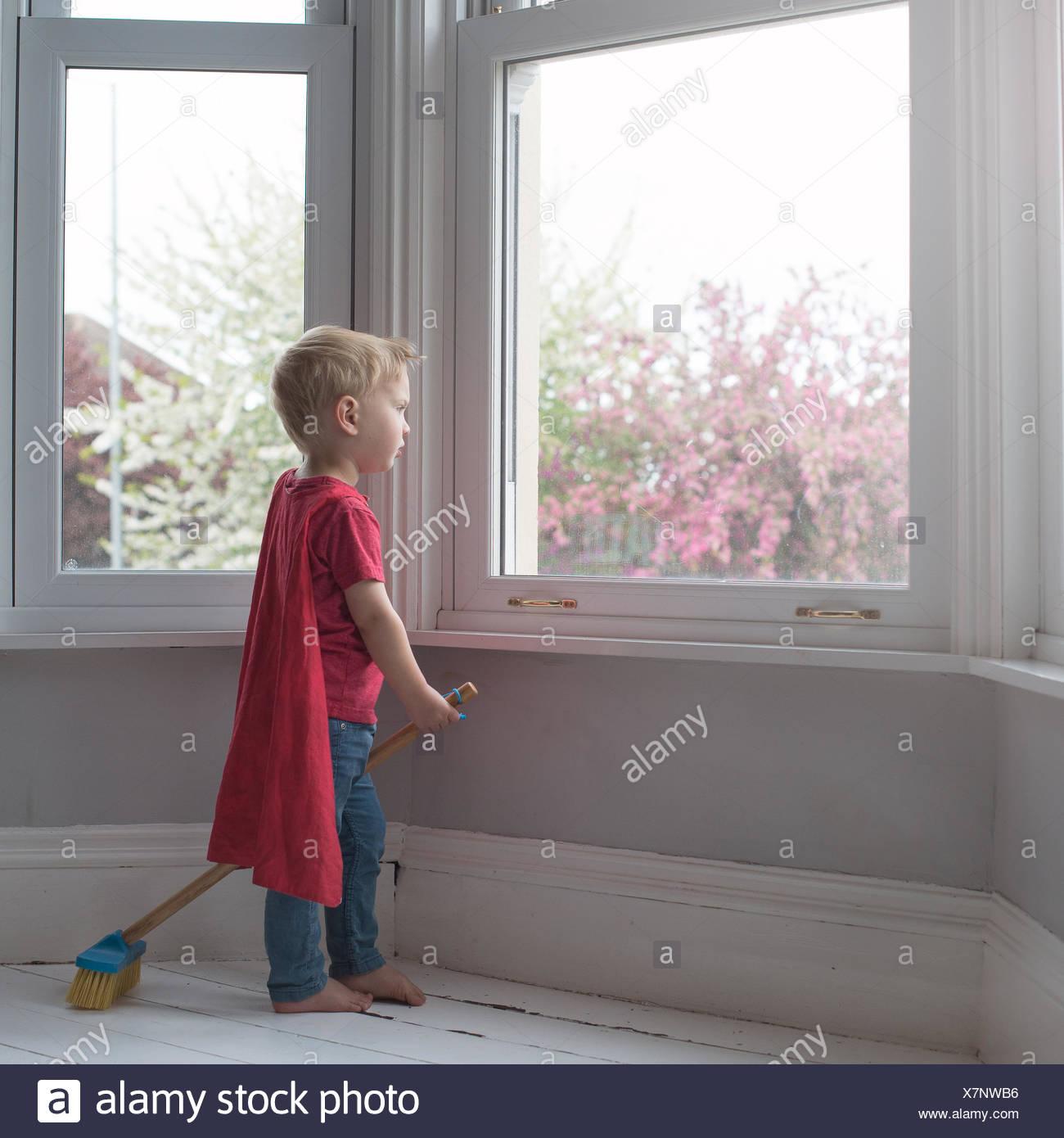 Junge gekleidet wie Superheld, Blick durch Fenster Stockbild