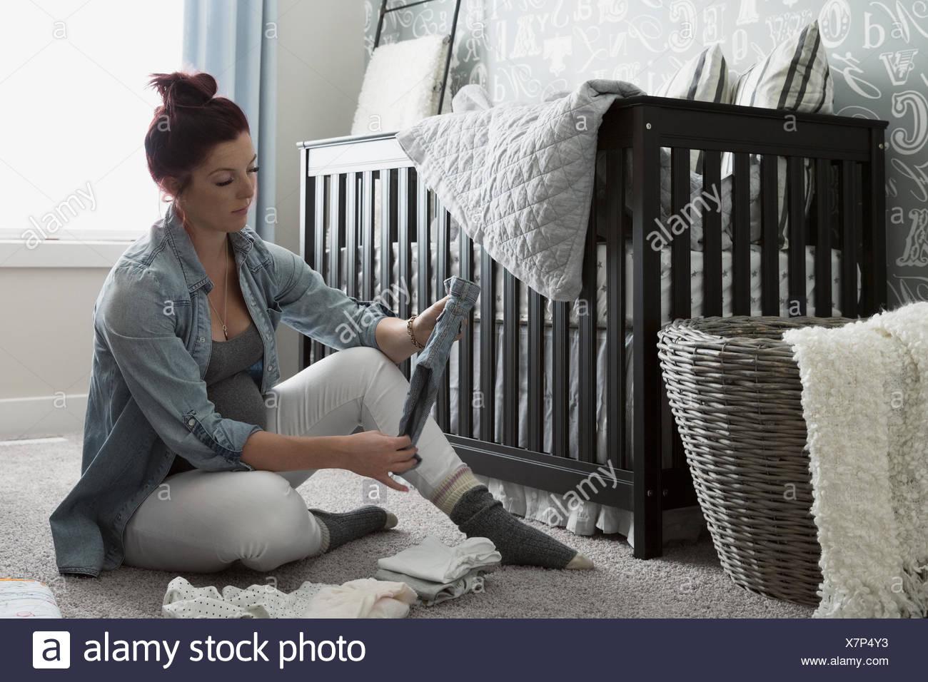 Schwangere Frau betrachten Baby-Kleidung im Kindergarten Stockbild