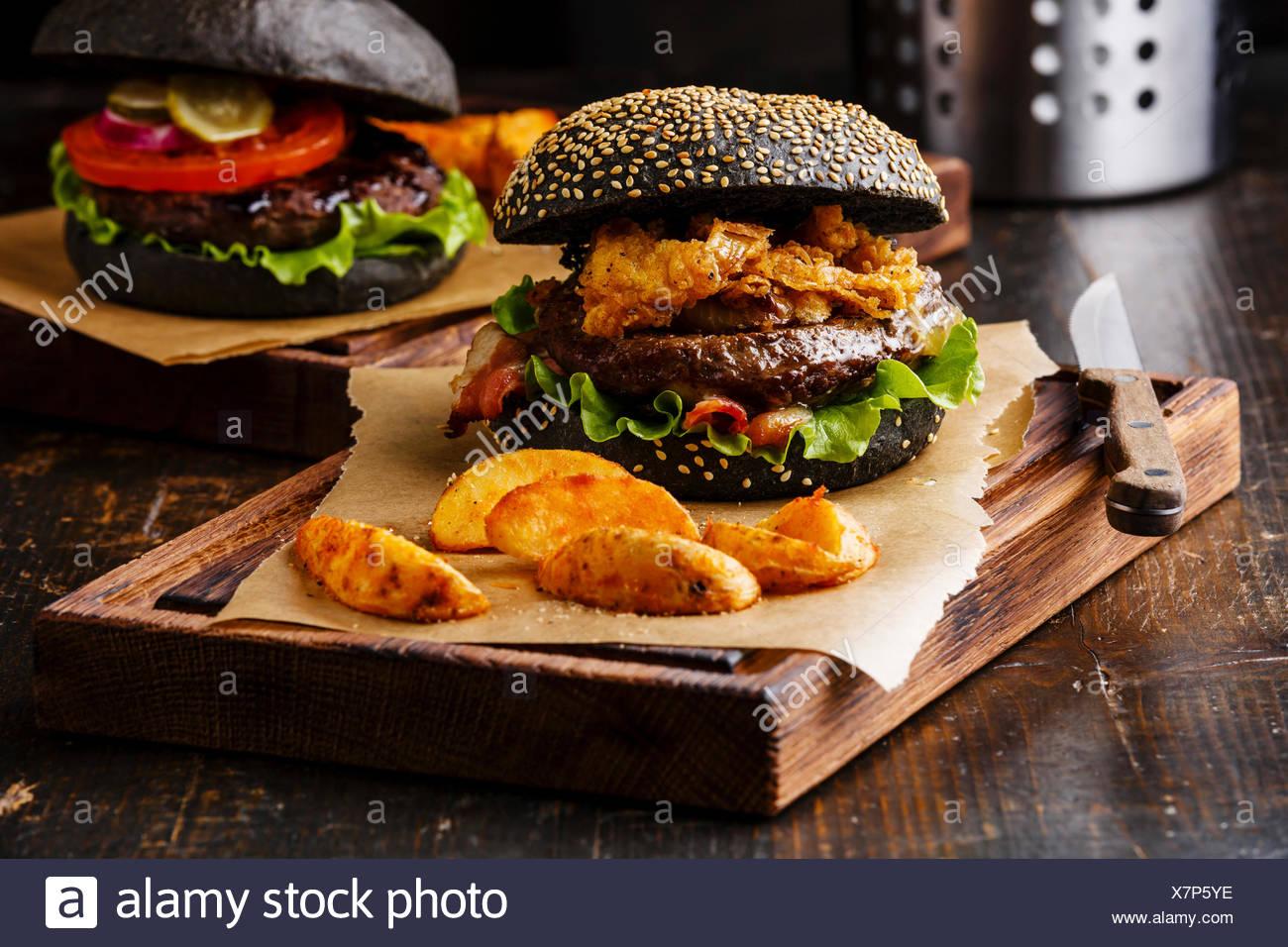 Schwarzen Burger mit Sesam Samen Brötchen Fleisch Speck Zwiebeln Pommes frites, Ringe und Kartoffelspalten auf dunklem Holz Stockfoto