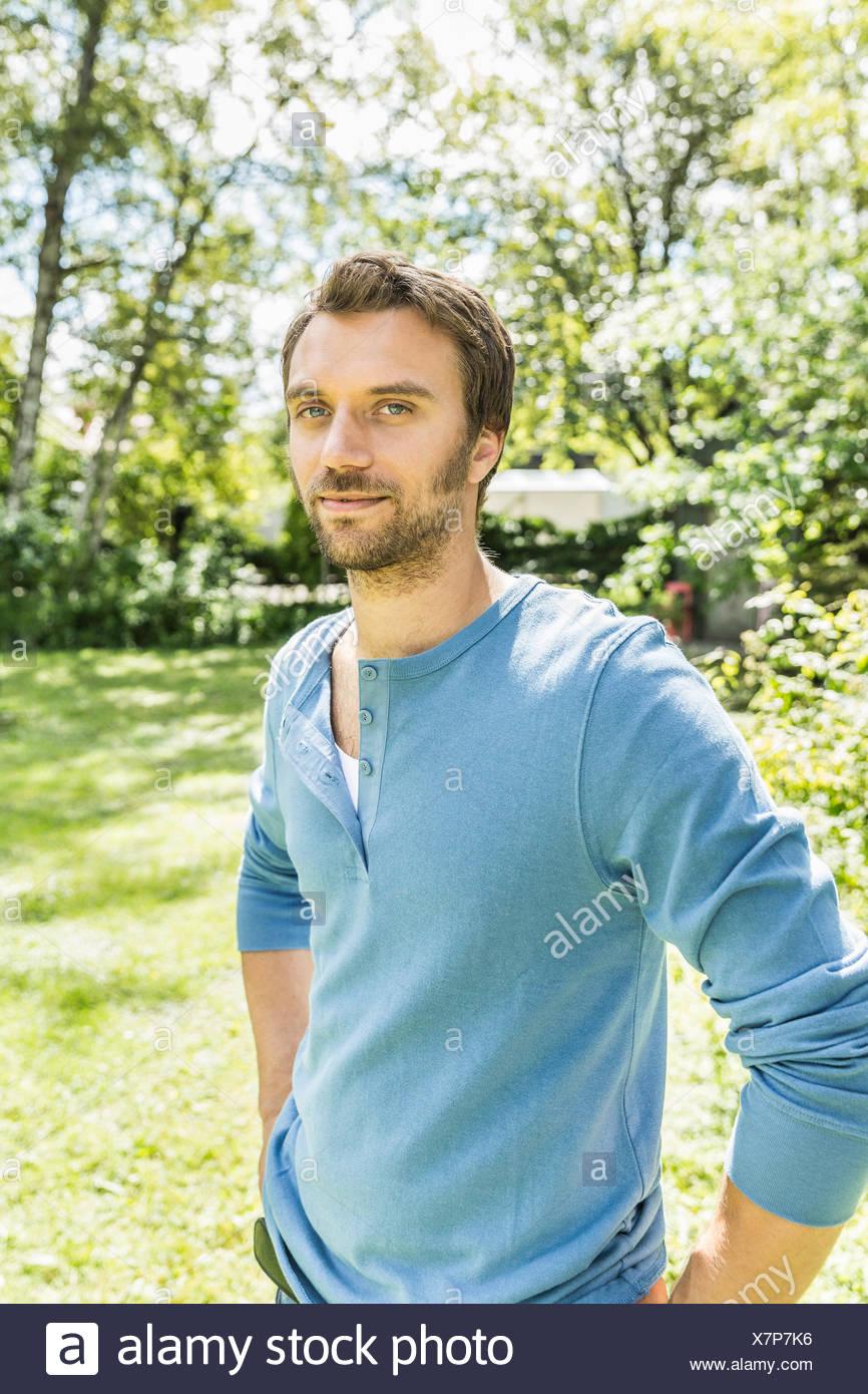 Porträt von zuversichtlich Mitte erwachsener Mann im Garten Stockfoto