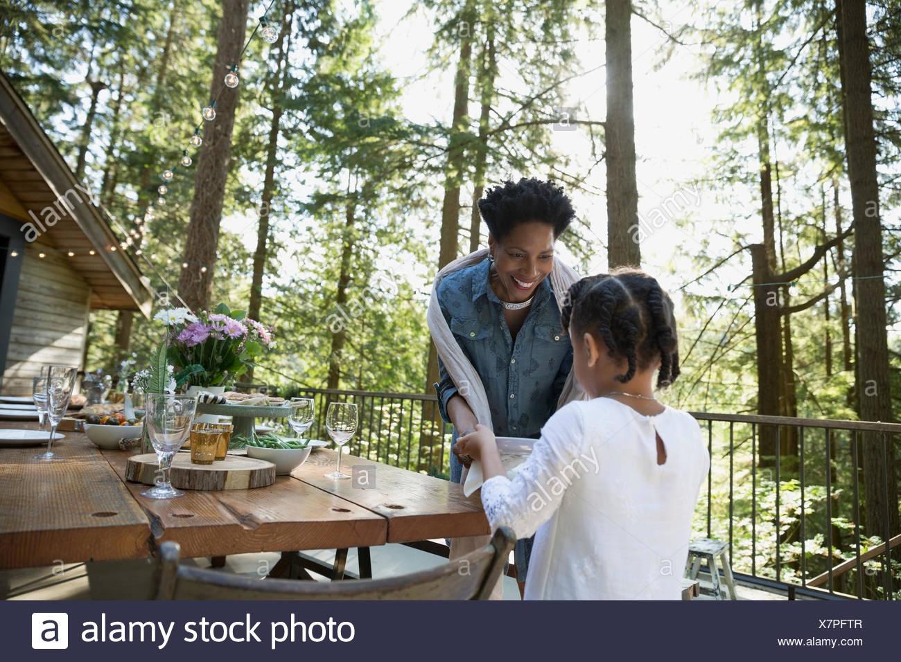 Enkelin hilft Großmutter Dinnerparty auf Kabine Balkon in Wäldern vorbereiten Stockbild