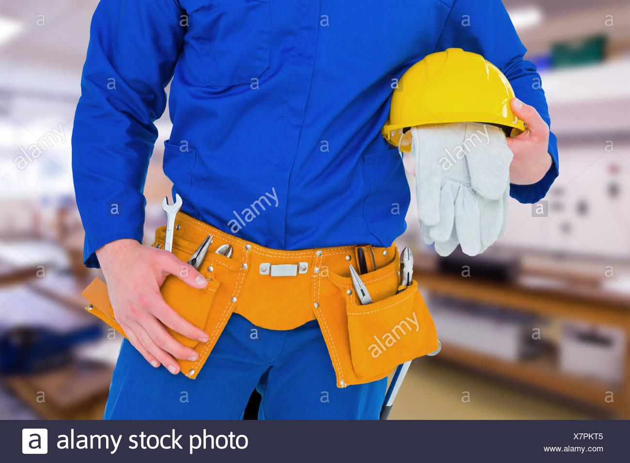 Zusammengesetztes Bild von Handyman holding Helm Stockbild