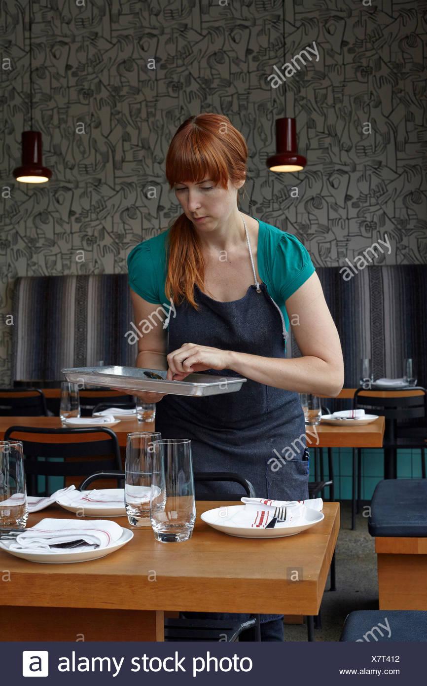 Mitte Erwachsene Frau Vorbereitung Tisch im restaurant Stockbild