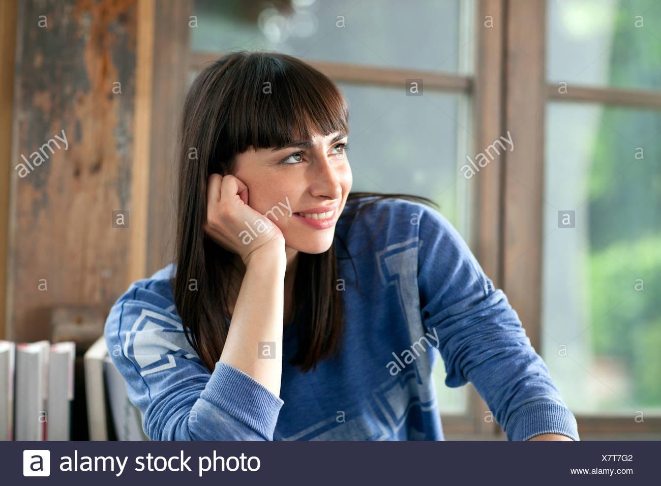 Porträt von Brünette Frau lächelnd mit Hand am Kinn Stockfoto