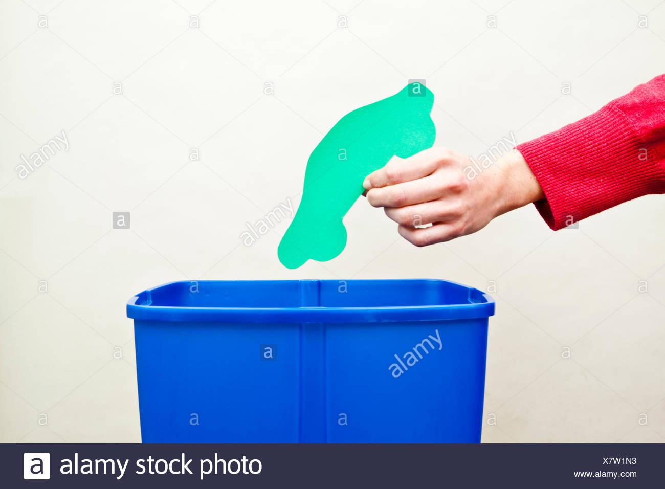 Zarte Frauenhand fallen Auto Form Papier ausgeschnitten in Recyclingbehälter Stockbild